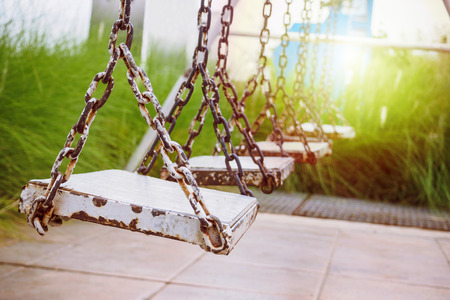 old wood swing in playground park Stock Photo