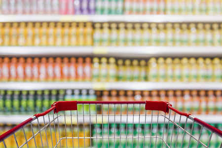 empty warehouse: Shopping cart view in Supermarket with beverage product Shelves in blurry for background Stock Photo