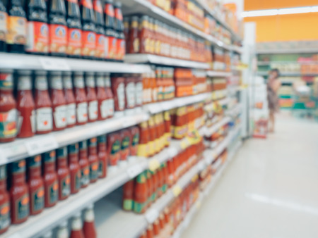 ketchup sauce seasoning bottles products in supermarket shelves blurred background Archivio Fotografico