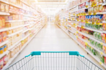 Shopping cart view in Supermarket aisle with product shelves abstract blur defocused background Standard-Bild