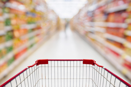 supermarket: Shopping cart view in Supermarket aisle with product shelves abstract blur defocused background Stock Photo