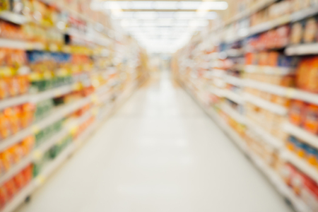 Supermarket aisle with product shelves abstract blur defocused background Stockfoto