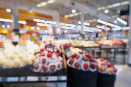 Grocery store with fresh fruits and vegetables shelves in supermarket blur defocused background