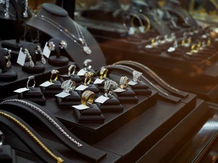 Gold jewelry diamond shop with rings and necklaces luxury retail store window display showcase Foto de archivo