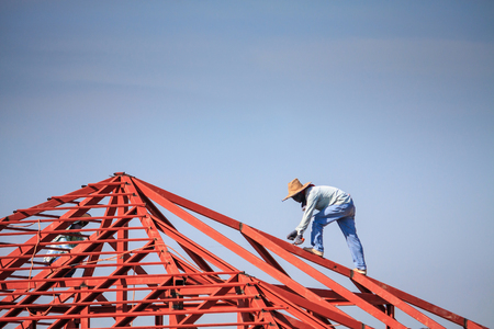 Construction welder workers installing steel frame structure of the house roof at building construction site with clouds and sky