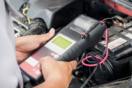 mechanic use voltmeter checking voltage of car battery in car service centre