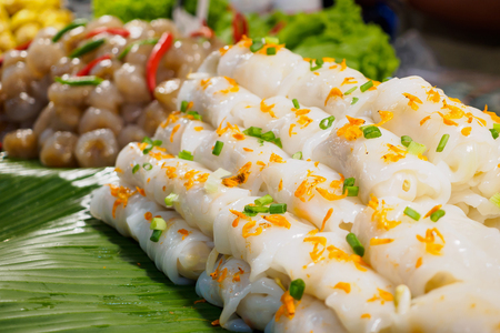 rice noodle crepe roll with shrimp, pork and vegetable on banana leaf