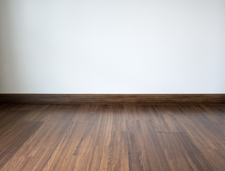 Empty room with laminate floor and white wall background