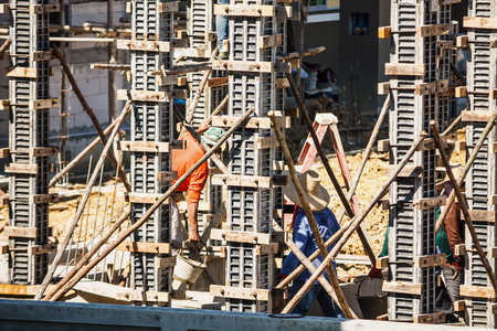 Worker pouring concrete to formwork frames at construction site to building house