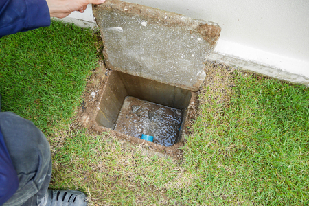 Worker hand open sewer cover of new house Stock fotó - 92832930