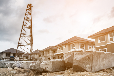 house building at construction site with pile driver and precast concrete piles