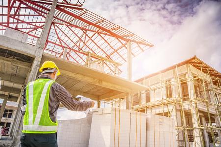 Asiatische Geschäftsmannbauingenieurarbeitskraft im Schutzhelm und in den Plänen tapezieren an Hand an der Hausbaustelle Standard-Bild