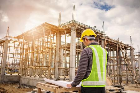 giovane uomo d'affari lavoratore ingegnere professionista presso il cantiere di costruzione casa con progetto Archivio Fotografico