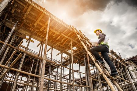 jonge professionele ingenieur werknemer in beschermende helm en blauwdrukken papier bij de hand werken op ladder op de woningbouw bouwplaats