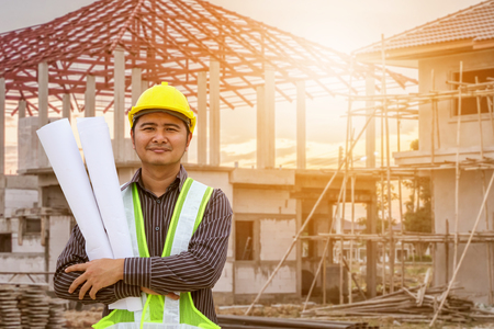 Asian business man construction engineer worker in protective helmet and blueprints paper on hand at house building site Zdjęcie Seryjne - 93656937