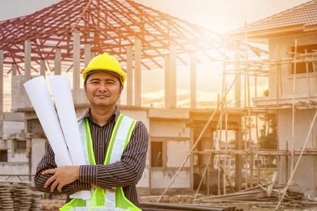 De Aziatische arbeider van de bedrijfsmensenbouwingenieur in beschermend helm en blauwdrukkendocument bij hand bij woningbouwplaats