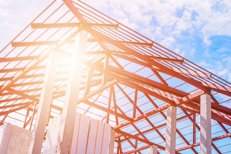 Steel roof frame structure of building house at construction site with blue sky clouds and sun light