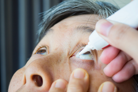 Doctor apply artificial tears gel to senior woman patient eye for treatment dry eye Stock Photo