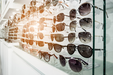 Sunglasses on display shelves in glasses store Standard-Bild