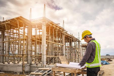 młody człowiek biznesu profesjonalny inżynier pracownik na placu budowy domu z planem