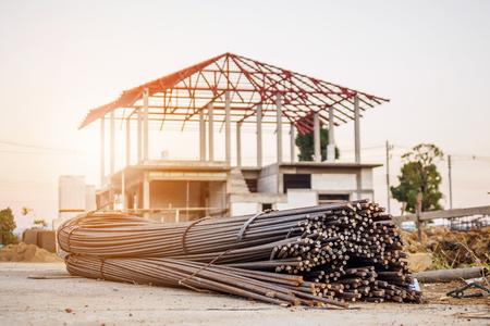 stalowe pręty zbrojeniowe do betonu zbrojeniowego na placu budowy z domem w tle budowy