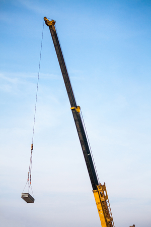 yellow telescopic arms of mobile construction crane truck lifting concrete slab to building house at construction site
