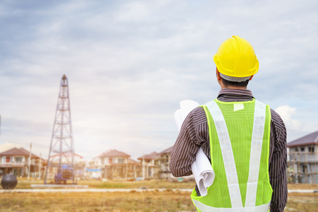 Asian business man construction engineer worker with protective helmet at house building site Stock Photo