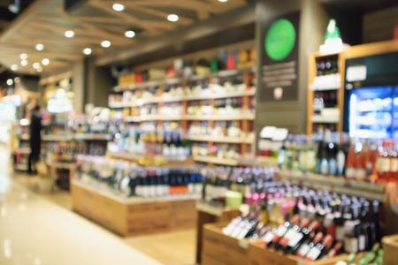 Bottiglie di vino astratte della sfuocatura sugli scaffali dell'alcool del liquore nel supermercato o nel deposito del vino Archivio Fotografico