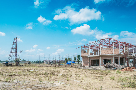 Residential new house building at construction site with clouds and blue sky Stock Photo