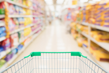Shopping cart with abstract blur supermarket discount store aisle and pet food product shelves interior defocused background 写真素材