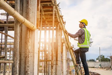Junger professioneller Ingenieurarbeiter im Schutzhelm und im Blaupausenpapier zur Handarbeit auf der Leiter auf der Baustelle des Hauses