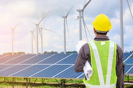 Junger Geschäftsmanningenieur mit gelbem Helm am Sonnenkollektor- und Windgenerator-Kraftwerksbaustellenhintergrund