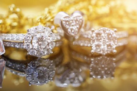 Anelli di diamanti gioielli in oro di lusso con la riflessione su sfondo nero