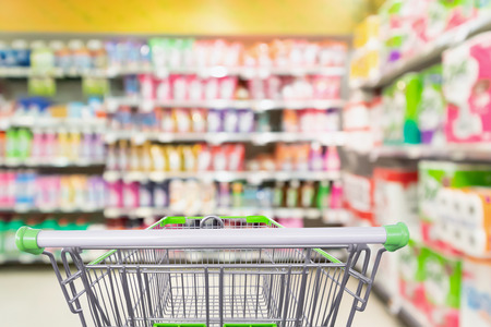 detergent and cleaning product shelves in supermarket or grocery store with empty shopping cart