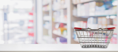 Empty shopping basket on pharmacy drugstore counter with blur shelves of medicine and vitamin supplements background