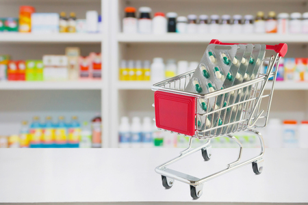 medicine pills blister pack capsule in shopping cart on pharmacy store counter with blur drugstore shelves defocused background