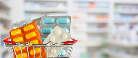 Medicine pill tablet in shopping basket with pharmacy drugstore shelves blurred background 版權商用圖片