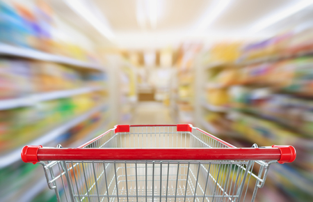 supermarket aisle blur abstract background with empty red shopping cart Stock Photo