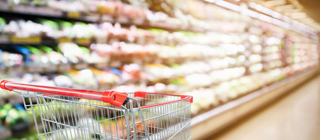supermarket grocery store with fruit and vegetable shelves interior defocused background with empty red shopping cart