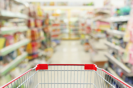 convenience store shelves interior blur background with empty supermarket shopping cart