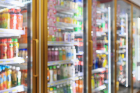 supermarket convenience store refrigerators with soft drink bottles on shelves abstract blur background Stockfoto