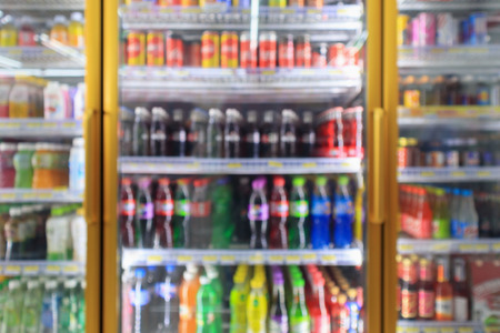 supermarket convenience store refrigerators with soft drink bottles on shelves abstract blur background Banque d'images
