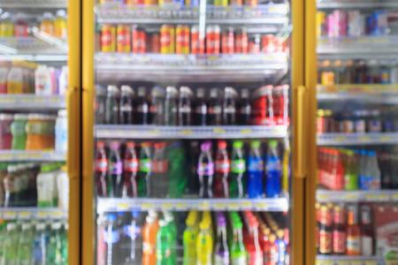 Réfrigérateurs de supérette de supermarché avec des bouteilles de boissons gazeuses sur des étagères arrière-plan flou abstrait