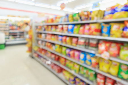 Supermarket convenience store shelves with Potato chips snack blur abstract background