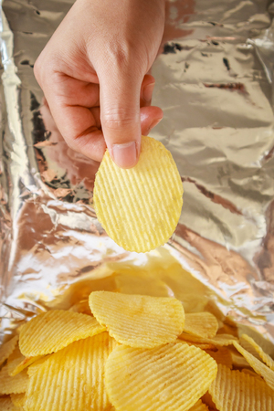 Hand hold potato chips inside snack foil bag 스톡 콘텐츠