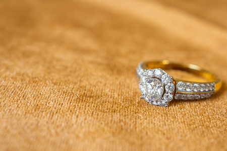 Jewelry diamond ring on golden fabric background close up