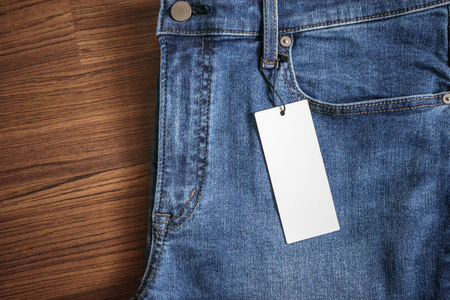 Blue jeans with blank white price label tag on wooden background