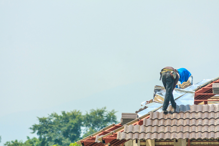 Construction roofer installing roof tiles at house building site Stock Photo