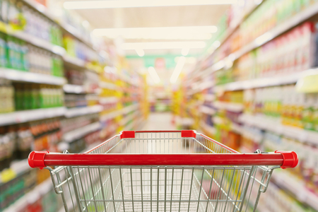 Supermarket aisle interior blur background with empty red shopping cart Stock fotó