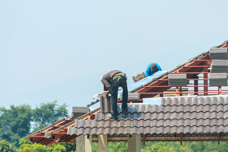 Construction roofer installing roof tiles at house building site Фото со стока